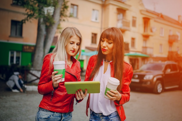 Frauen mit kaffeetassen und einer tablette