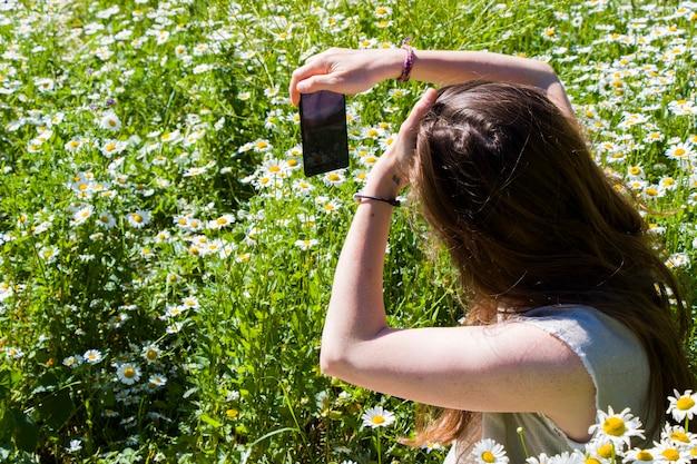 Frauen mit kleid machen foto im feld von gänseblümchen, reisethema