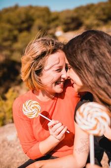 Frauen mit lollipops, die nasen berühren