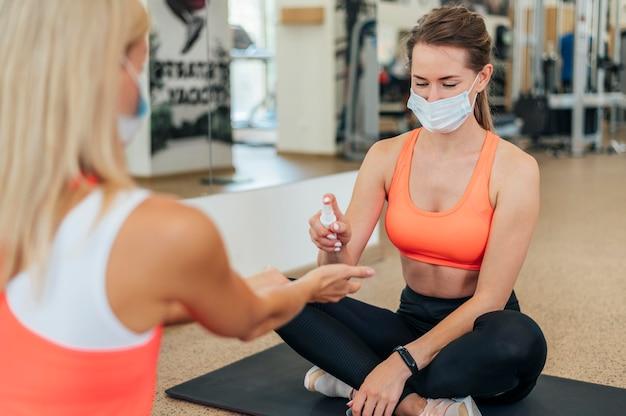 Frauen mit medizinischen masken desinfizieren ihre hände im fitnessstudio