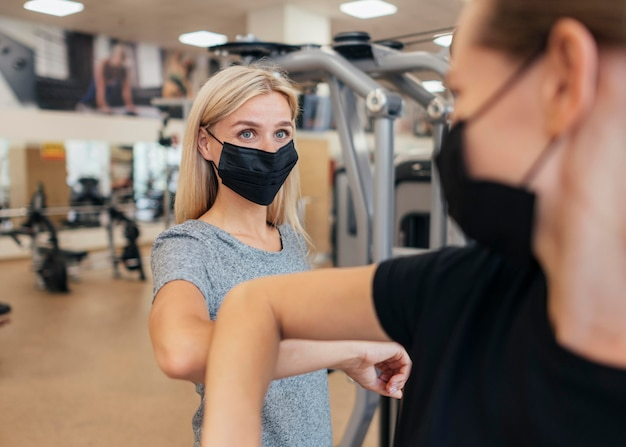 Frauen mit medizinischen masken, die den ellbogengruß im fitnessstudio üben