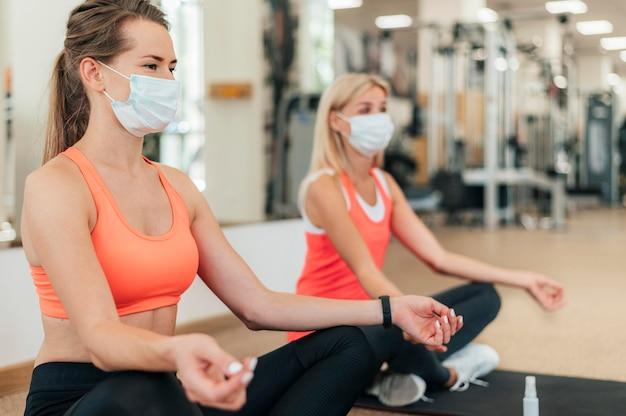 Frauen mit medizinischen masken, die yoga im fitnessstudio tun