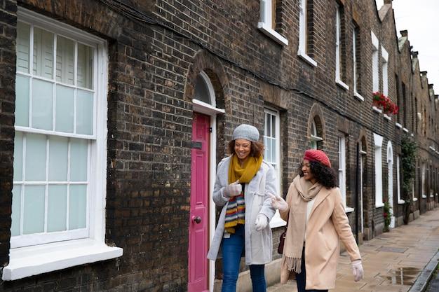 Frauen mit mittlerem schuss, die in der stadt spazieren gehen