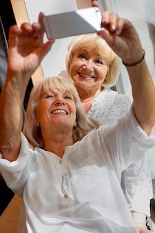 Frauen mit mittlerer aufnahme, die ein selfie machen