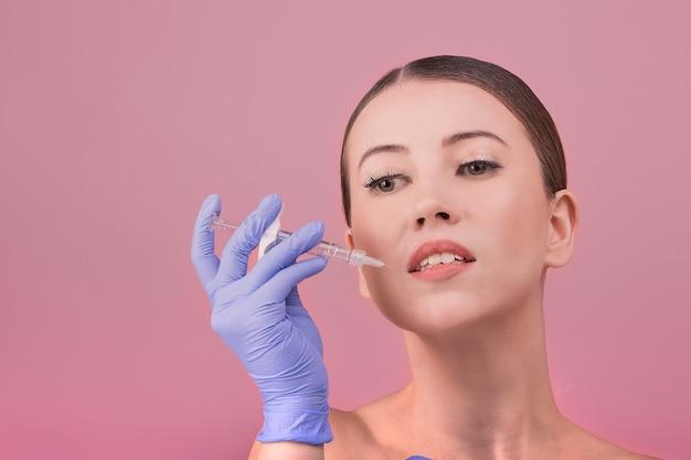 Frauen mit perfekter hauthaltung halten eine spritze in der hand