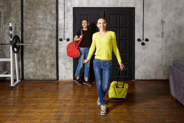 Frauen mit reisetaschen betreten die loft-wohnung nach der rückkehr von einer touristenreise