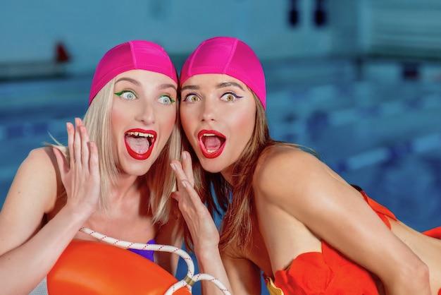 Frauen mit stylischem make-up in badekappen und badeanzügen im schwimmbad überrascht