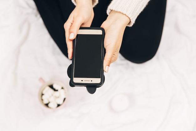 Frauen mit telefon. minimales foto, weißer hintergrund. ansicht von oben. mock-up.