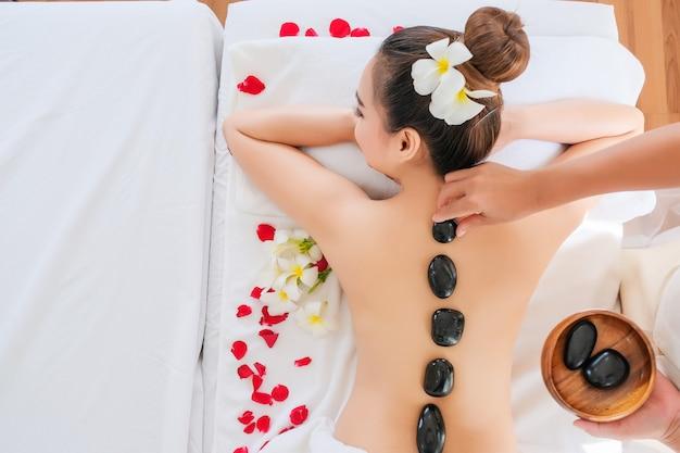 Frauen mit therapeutischen steinen auf dem rücken