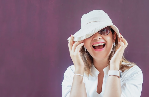Frauen mit weißem hut und weißem kleid mit sonnenbrille