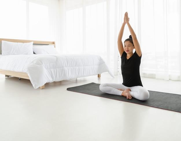 Frauen mittleren alters, die yoga in leichter sitzhaltung (sukhasana) mit erhobenen händen über der kopfhaltung praktizieren. meditation mit yoga im weißen schlafzimmer