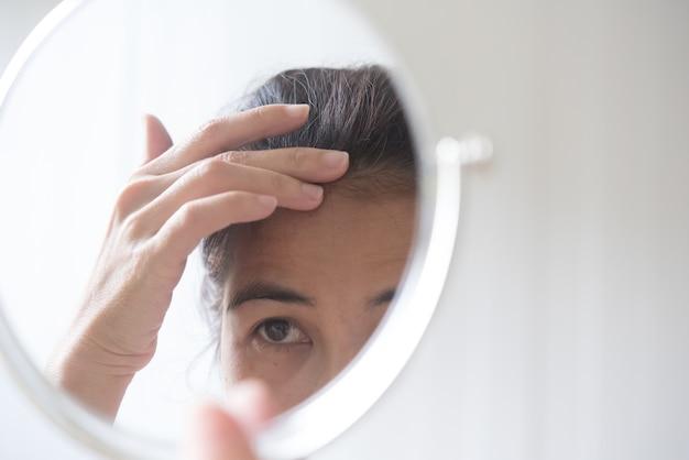 Frauen mittleren alters sind bestürzte haarausfallprobleme.