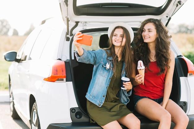 Frauen nehmen selfie am kofferraum