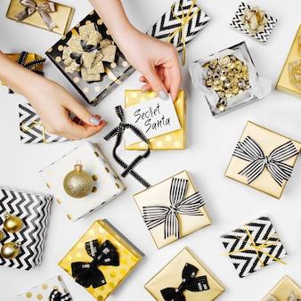 Frauen organisieren schön verpackte weihnachtsgeschenke auf weißem hintergrund, ansicht von oben
