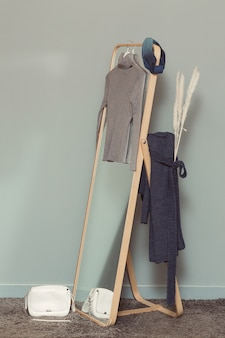 Frauen-polohals und -hose hängen am spiegel und eine weiße tasche auf dem boden.