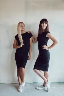 Frauen posieren an der wand