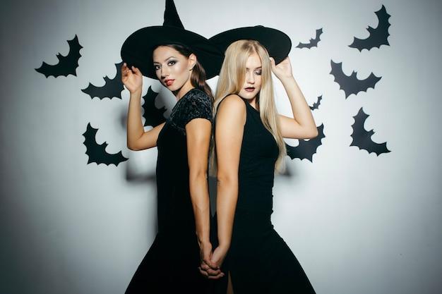 Frauen posieren in hüte für halloween