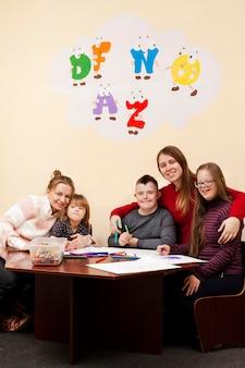 Frauen posieren mit kindern mit down-syndrom
