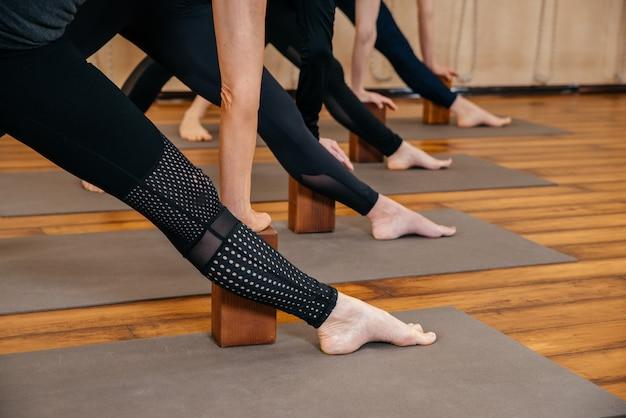 Frauen praktizieren yoga-stretching mit holzklötzen mit den händen, übung für wirbelsäule und schultern
