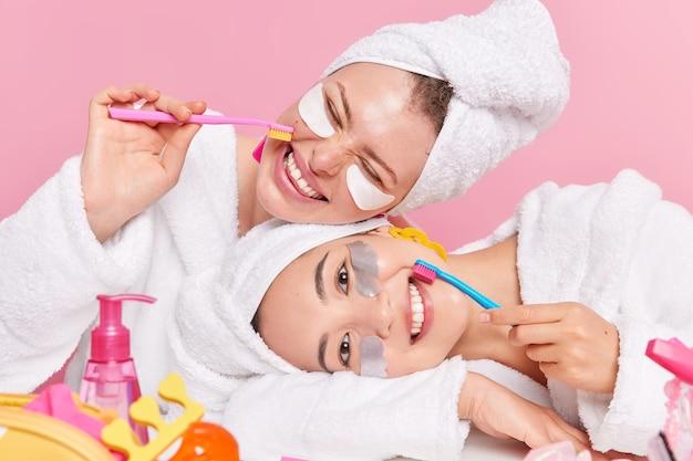 Frauen putzen regelmäßig die zähne mit zahnbürsten tragen schönheitspflaster unter den augen auf und tragen legere hauskleidung. genießen sie die täglichen hygienemaßnahmen.