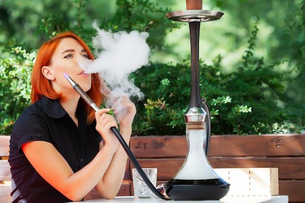 Frauen rauchen eine wasserpfeife in einem café auf der straße.