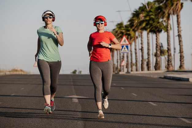 Frauen rennen die straße entlang und hören musik