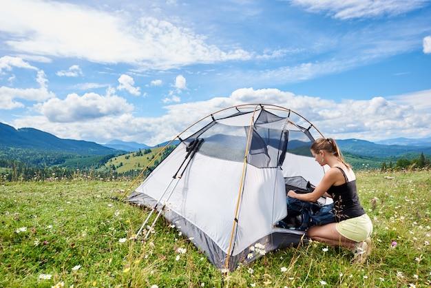 Frauen-rucksacktouristen, die bergpfad wandern, sachen in rucksack packen, sonnigen sommermorgen in bergen genießen