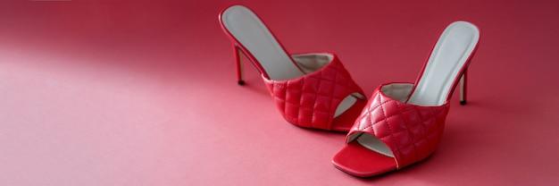 Frauen sandalen mit hohen absätzen, die auf rotem hintergrund nahaufnahme stehen