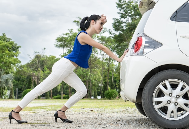 Frauen schieben das auto. war an der seite gebrochen