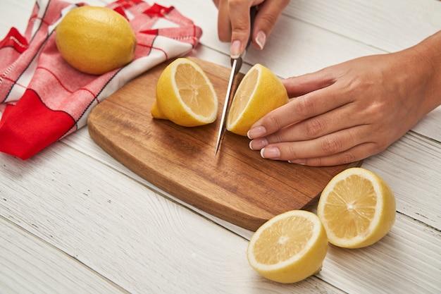 Frauen schneiden eine zitrone mit einem messer