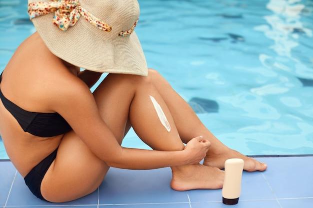 Frauen schöne sexy beine auf dem pool. hautpflege und schutz sonne