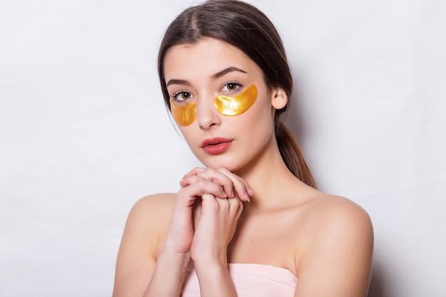 Frauen-schönheits-gesicht mit maske unter augen. schöne frau mit natürlichem make-up und goldenen kollagenflecken auf frischer gesichtshaut. hohe auflösung