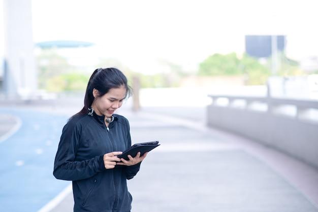 Frauen sehen lächeln und glücklich aus mit schwarzer sportbekleidung, die das tablet hält und berührt.