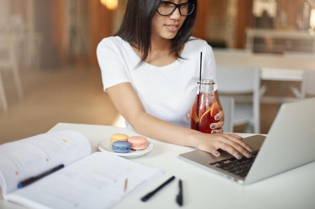 Frauen sind schlau. junge frau, die einen laptop verwendet, der zur gleichen zeit limonade in einem café trinkt und darauf wartet, ein macaron-gebäck zu essen.