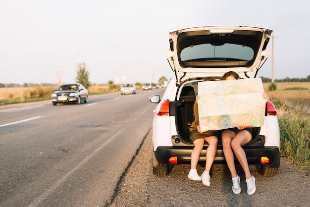 Frauen sitzen auf dem auto mit karte