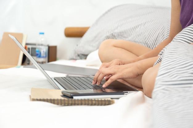 Frauen sitzen auf dem bett im schlafzimmer, das mit computer arbeitet.