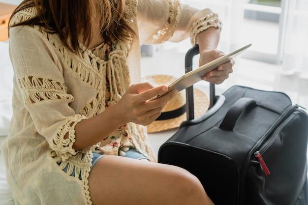 Frauen sitzen auf dem bett mit tablette im hotel.