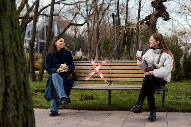 Frauen sitzen auf distanz und tragen maske