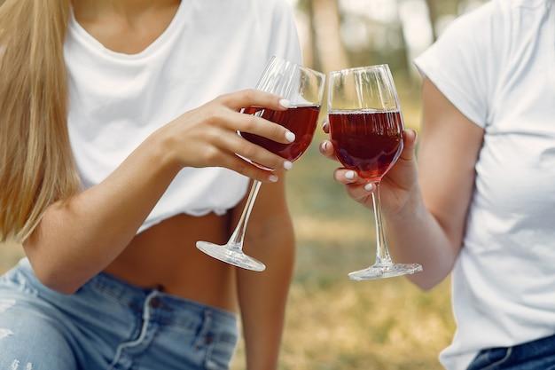 Frauen sitzen auf einem picknick und trinken wein