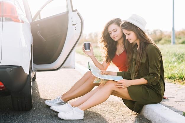Frauen sitzen auf grenze mit karte