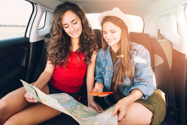 Frauen sitzen im auto mit karte und telefon