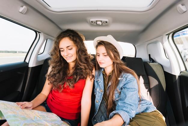 Frauen sitzen im auto mit karte