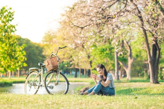 Frauen sitzen und hören musik vom smartphone im garten und fahrrad.