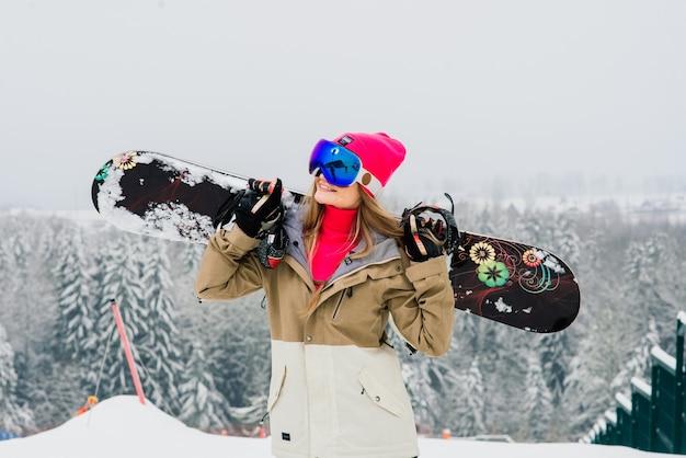 Frauen-snowboarder, der mit snowboard steht. nahaufnahmeporträt einer fröhlichen frau an der spitze der skipiste