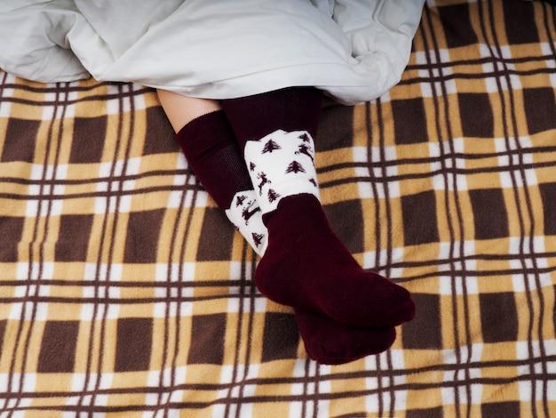 Frauen-sofabett-rest-plaid-weicher getonter lebensstil, füße mit socken, braunes plaid