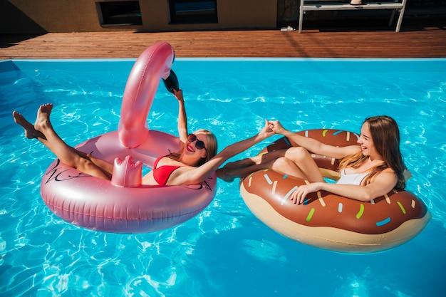 Frauen spielen im pool mit schwimmringen