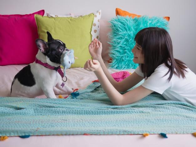 Frauen spielen mit hunden auf dem bett