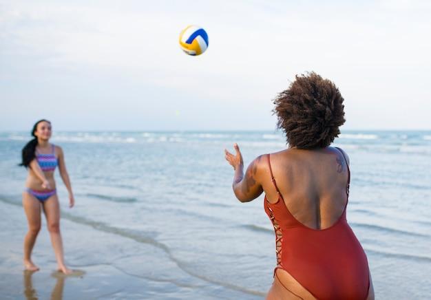 Frauen spielen volleyball am strand