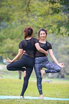 Frauen spielen yoga im fitnessstudio. trainieren