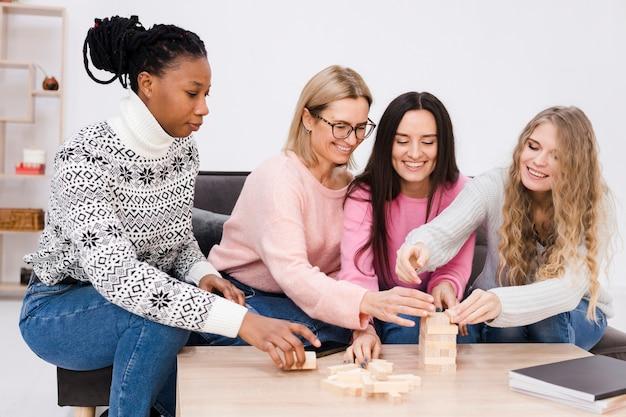 Frauen spielen zusammen ein holzturmspiel